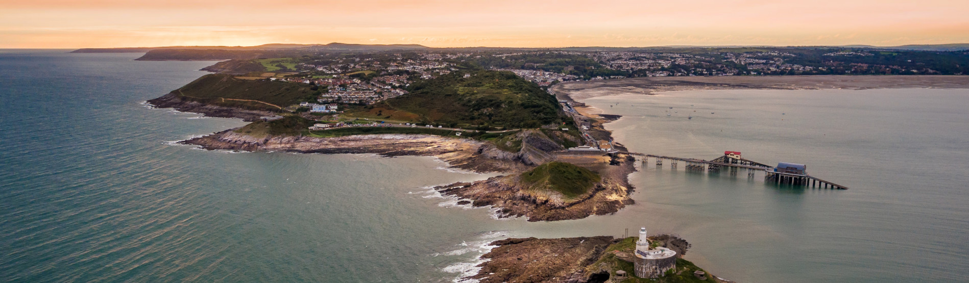 Image shows an aerial shot of Mumbles headland and lighthouse.